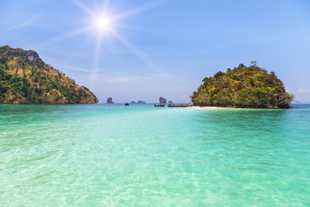 snorkelers: view of small tropical limestone island with sunlight in the andaman sea at Thailand.
