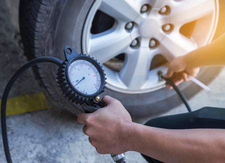 Close up mechanic inflating tire and checking air pressure with gauge pressure 免版税图像 - 75485157