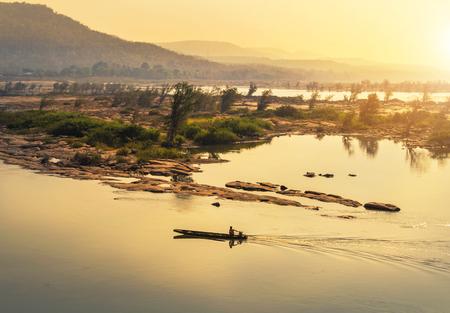 タイとラオスのコンジャム地区のタイ国境の日の出にメコン川でセーリング木造漁船