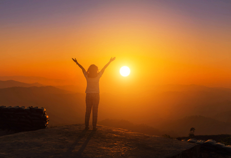silhoutte young asian womanstand raised up arms enjoying to valley view on high cliff over rainforest mountains in sunset Foto de archivo