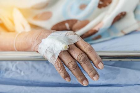 病院のベッドに横たわって高齢者患者の手で注入プラグの静脈カテーテルを閉じる