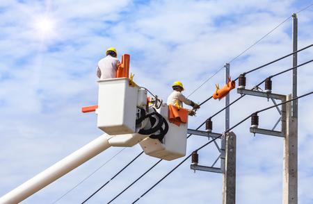 Elektriciens die draad van de machtslijn herstellen met emmer hydraulisch opheffend platform op blauwe hemelachtergrond