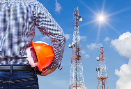 engineer holding safety helmet with telecommunication tower pillars  under blue sky background