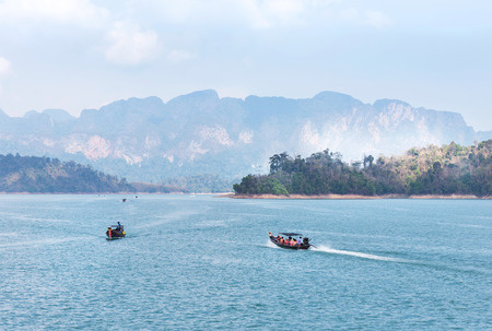 longtail boat and motorboat sailing in lake of ratchaprapha dam at khao sok national park, Surat Thani province,Thailand