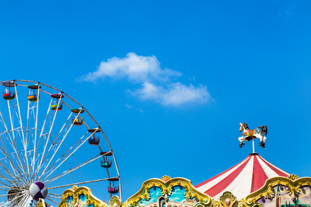 antique carousel horses tent in amusement park with colourful ferris wheel on blue sky background