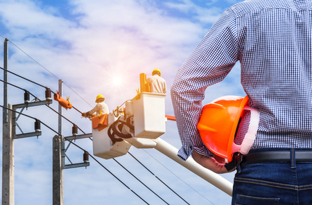 Electrical engineer holding safety helmet with electrician working on electric power pole with  bucket hydraulic lifting platform on blue sky background Stock Photo