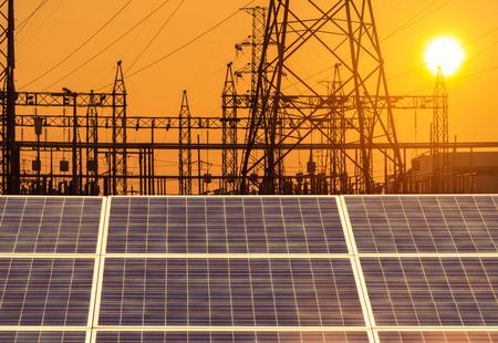 zonnecellen in elektriciteitscentrale alternatieve energie van de zon met hoogspanning elektrische pyloon pijlers hulpkantoor op zonsondergang.