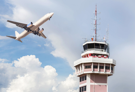 Air traffic control tower in international airport with passenger airplane jet taking off on blue sky background