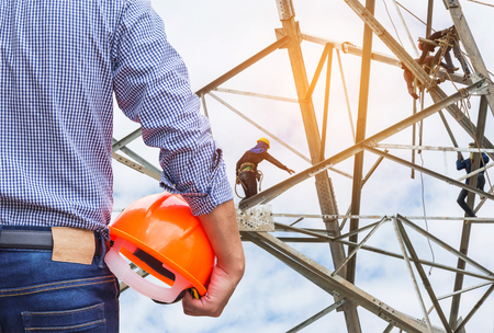 ingenieur die gele veiligheidshelm houden met elektriciens die bij pylon bouwtoren werken in bouwwerf