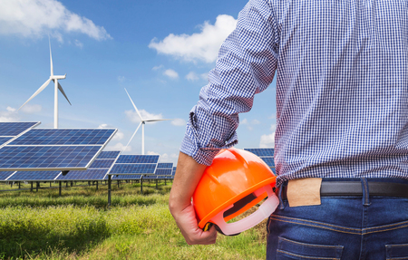 Engineer stand holding safety yellow helmet with solar cells and wind turbines generating electricity in power station site alternative renewable energy from natural Stock Photo