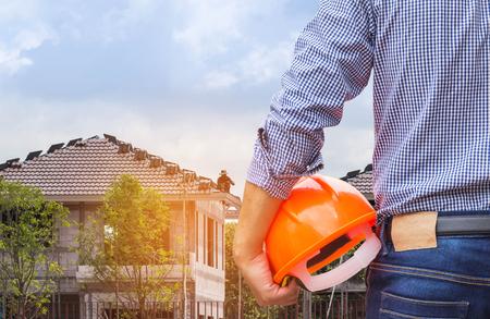 mieszkaniec inżynier gospodarstwa żółty kask ochronny w nowym domu budynku w budowie