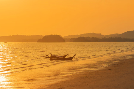 Longtail boats moor in tropical andaman sea during sunset time at Krabi, Thailand