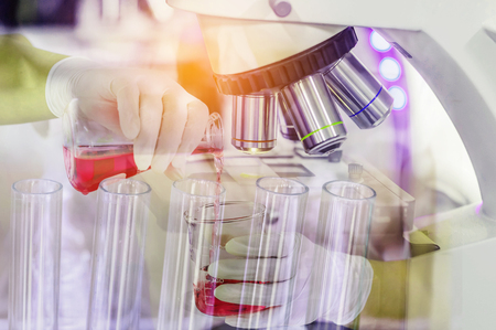 Double exposure close up scientist woman research carrying chemistry liquid with microscope equipment for research experiments to test tube at science laboratory Stock Photo