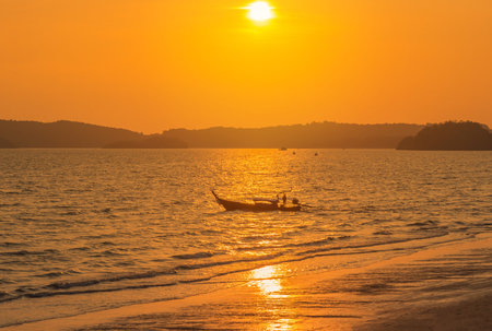Longtail boat sailing in tropical andaman sea during sunset time at Krabi, Thailand