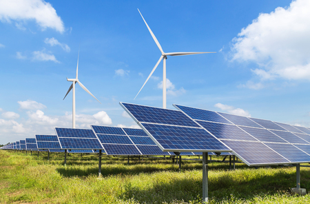Solar panels and wind turbines generating electricity is solar energy and wind energy in hybrid power plant systems station use renewable energy to generate electricity with blue sky background Stock Photo