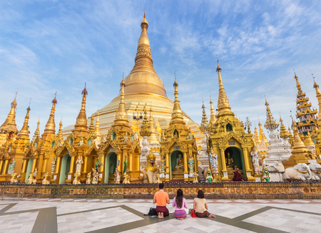 family burmese people  praying respects at Shwedagon big golden pagoda most sacred Buddhist pagoda in rangoon, Myanmar(Burma) on blue sky
