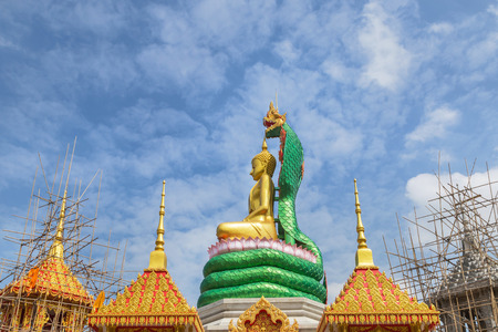 big golden buddha statue during construction sitting in public  thai temple on blue sky background