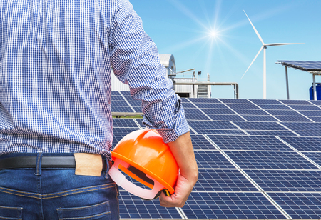 Engineer stand holding safety yellow helmet with solar cells and wind turbines generating electricity in hybrid power plant systems station use renewable energy to generate electricity alternative renewable energy from natural Stock Photo