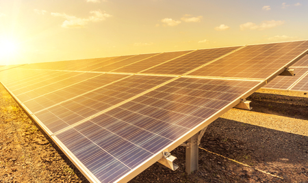 Close up rows array of polycrystalline silicon solar cells or photovoltaics in solar power plant turn up skyward absorb the sunlight from the sun use light energy to generate electricity on sunset Stock Photo
