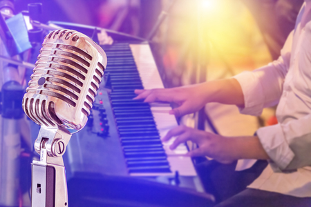 Close up retro microphone with musician playing keyboard synthesizer on band in night concert background Banque d'images