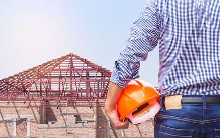 resident engineer holding yellow safety helmet with steel roof frame structures at new home building under construction site residential development concept