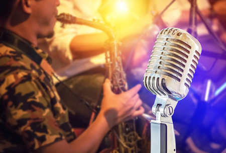 Close up retro microphone with musician playing saxophone on band in nigh concert background Stock Photo