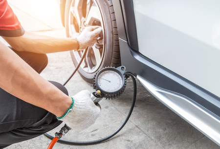 Close up mechanic inflating put air into the tyre and checking air pressure with gauge pressure in service station 스톡 콘텐츠 - 111656161