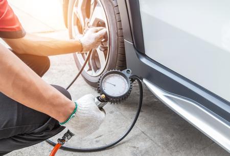 Schließen Sie den Mechaniker, der Luft in den Reifen aufpumpt und den Luftdruck mit dem Manometerdruck in der Tankstelle überprüft