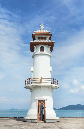 Landscape view of public white lighthouse on pier of Bang Bao fishing village with fishing boats mooring at Koh Chang Island,Trat, Thailand