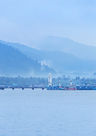 Landscape view of public lighthouse on pier of Salak Phet fishing village  Salak Phet bay at Koh Chang Island , Trat Thailand with white fog in early morning