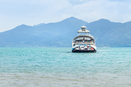 Large ferryboat carrying passengers and cars crossing in blue sea  between Koh Chang island and Trad province, Thailand