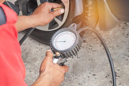 Gros plan mécanicien gonflant l'air mis dans le pneu et vérifiant la pression d'air avec la pression manométrique dans la station-service Banque d'images