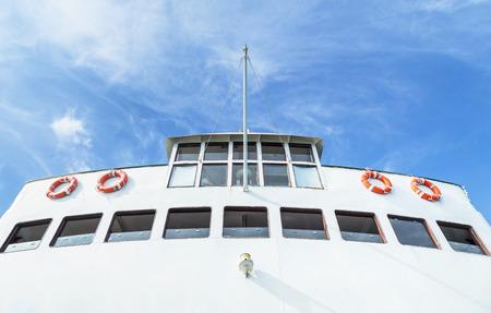 Safety orange life buoys safety equipment on white ferry boat ship with blue sky Standard-Bild - 111687813