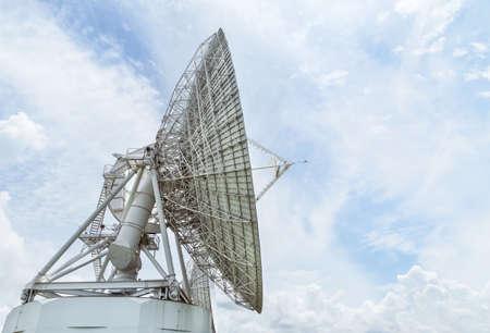 Big large white satellite dishes against blue sky