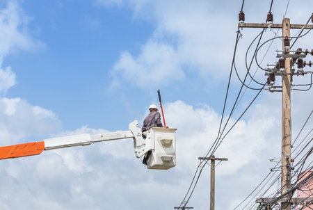 Electrician repairing wire of the power line with bucket hydraulic lifting platform on blue sky