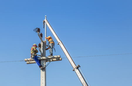 Electricians climbing work in the height on concrete electric power pole with crane Reklamní fotografie