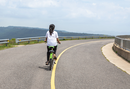 back view the girl enjoying ride bicycle relaxation on road dam ridge of Lam Takhong reservoir dam, Nakhon Ratchasima, Thailand