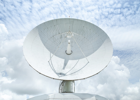 Big large white satellite dishe turn up skyward on blue sky in communication antenna system center station