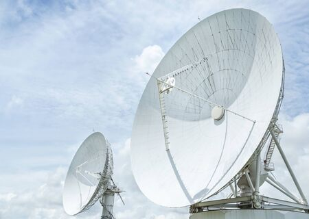 Large radio antenna astronomy dish turn up skyward on blue sky in earth communication antenna system center station Banque d'images