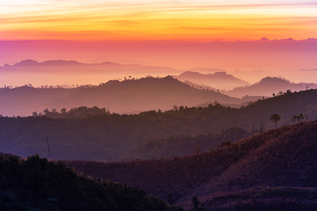 Landscape view of sunrise in early morning on high angle view with misty covered over layers mountain hills at thailand Reklamní fotografie