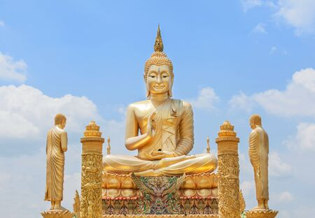 big golden buddha statue sitting in public thai temple under blue sky