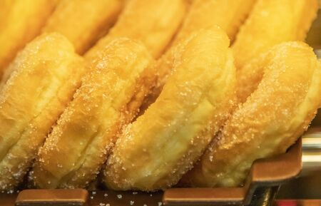 Close up row of sweet golden donuts cover with sugar