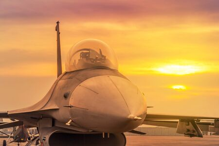 Silhouette fighter jet military aircraft parked on runway in twilight sunset time 免版税图像