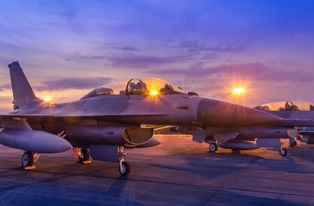 Silhouette fighter jet military aircraft parked on runway in twilight sunset time with light airport during air flight show in the night