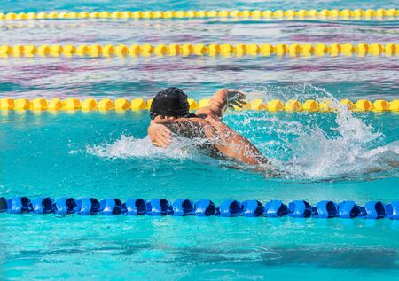male athlete swimmer swimming butterfly strokes in pool competition 免版税图像