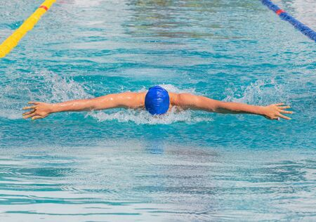 athlete swimmer swimming butterfly strokes in pool competition