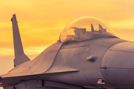 fighter jet military aircraft parked on runway standby ready to take off on sunset