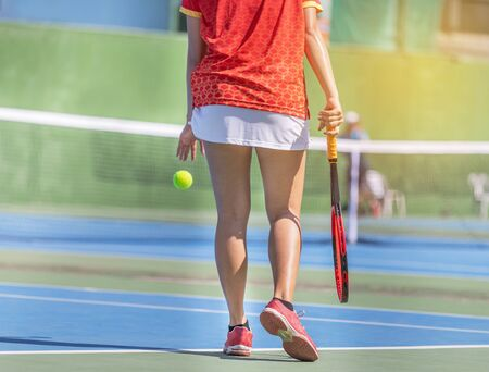 female tennis player with racket preparing to play tennis during competition in the tennis court on sunny day. 免版税图像