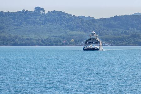 Large ferry boat carrying passengers and cars crossing in blue sea  between Koh Chang island and Trad province, Thailand cargo logistics transportation delivery concept.