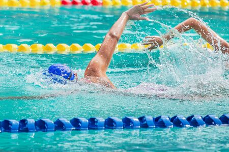 Movement of athletic  swimmers swimming freestyle stroke front crawl or forward crawl during competition in to the pool 免版税图像